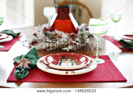 Christmas Table Holiday Dining Dinner Setting Arrangement. Christmas dinner set on the round table lit by morning light. Ideas for Christmas interior design.