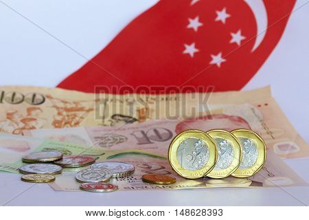 Singaporean one dollar coins with notes, coins and a flag as background.