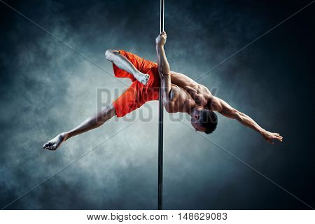 Young strong pole dancing man with smoke effect
