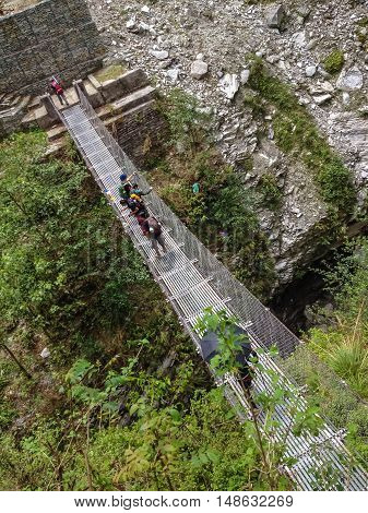 ANNAPURNA NEPAL - APRIL 14 2012 : Trekker walk across bridge on the way to Annapurna Base Camp Nepal