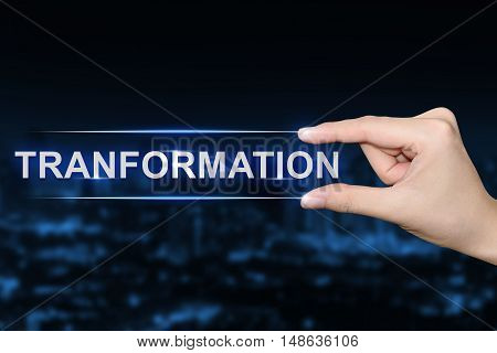 hand pushing transformation button on blurred blue background