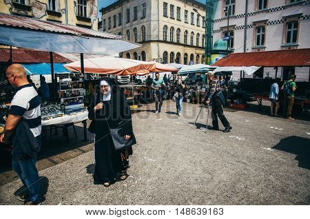 KRAKOW POLAND - JUNE 27 2015: A nun is on the market which is located in the Jewish quarter of Kazimierz.