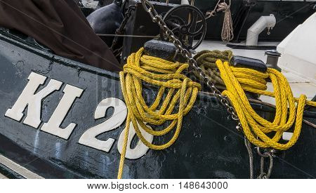 Enkhuizen The Netherlands - August 9 2016: Bollard on a black ship Number KL26 with yellow ropes.