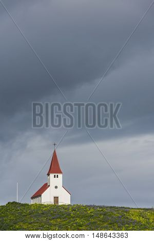 White church Vikurkirkja with red roof in Vik i Myrdal with dark clouds on Iceland.