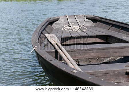 Wooden oars in rowing boat on lake.