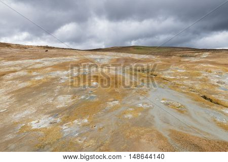Geothermal landscape Krafla on Iceland with red dirt steam and a hot water stream down a hill.