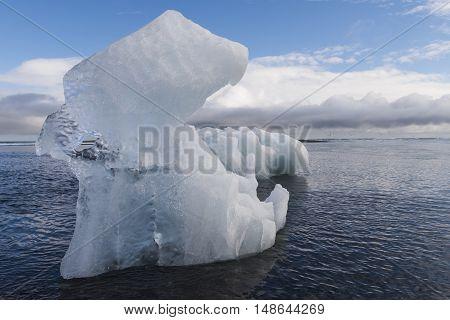 Ice block on beach and Artic Terns near river Jokulsa at Jokulsarlon glacier lagoon in the Vatnajokull National Park Iceland.