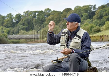 Fly-fisherman sitting on rock, choosing fly