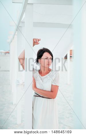 Woman, brunette with short hair in white dress on the beach of ocean, sea near sun shade, tent.