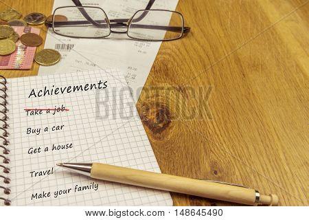 Achievements list in a spiral notebook - List of achievements written down in a spiral notebook on a wooden desk