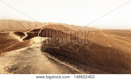 Desert dirty road near on white sky in Peru.