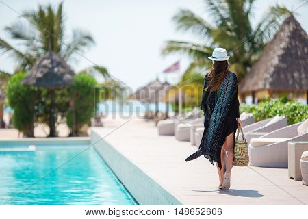Beautiful woman enjoying summer vacation near pool