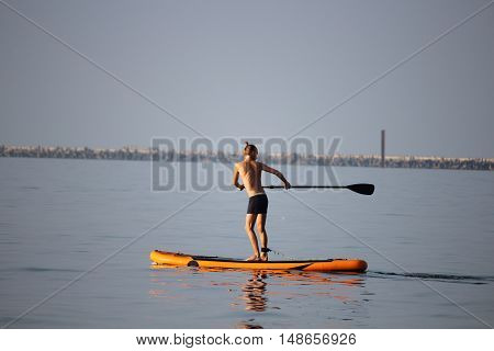the man young with an oar by the boat in the sea