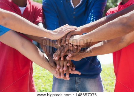 Mixed race group putting hands together to show partnership
