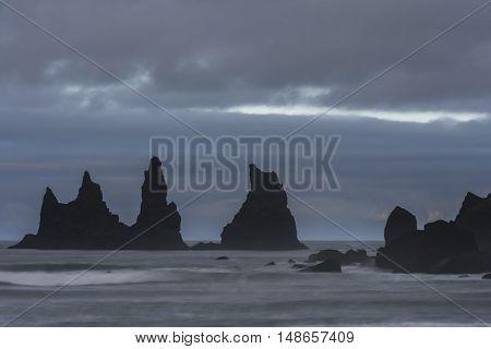 Reynishverfisvegur Reynisfjara black sand beach with rocks ocean and dark rain and storm clouds near the village of Vik in Iceland.