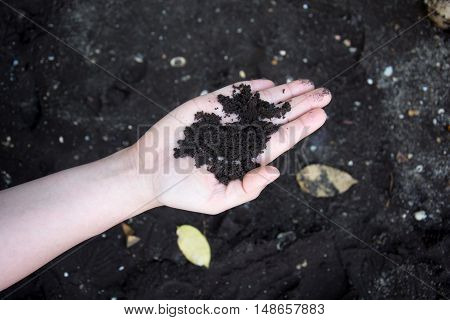 Black sea sand on woman hand in Trat Thailand