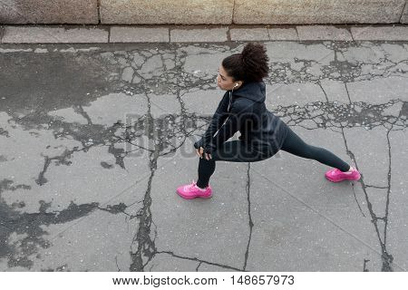Overhead view of young female runner prepares for workout on city street