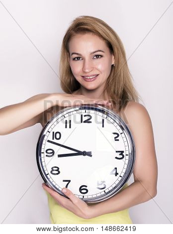 Beautiful young woman looking at a large silver retro clock that she is holding, she wonders how much time passed