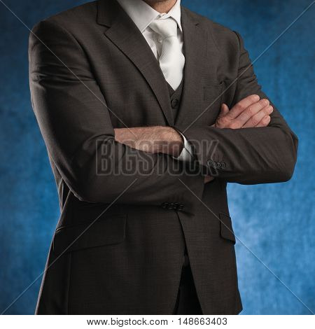 Business man standing with his arms crossed on a blue background stock picture