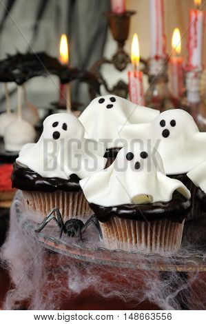 Smorgasbord сupcakes in chocolate glaze decorated marzipan ghosts on Halloween
