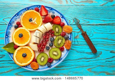 Fruit salad breakfast orange banana kiwi berries ow turquoise table