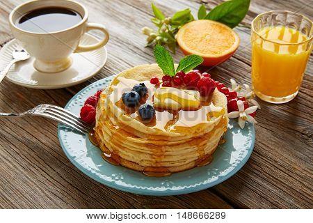 pancakes breakfast syrup coffee and orange juice with berries