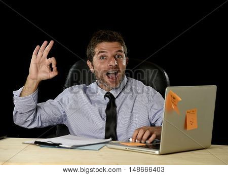 corporate portrait of happy successful businessman in shirt and tie smiling at office desk working with laptop computer isolated on black background confident and trustful in business success concept