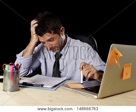 young tired businessman suffering work stress wasted and worried busy in office late at night with laptop computer in business problem and mess concept isolated on black background