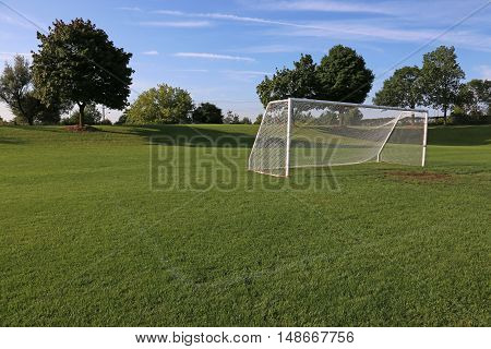 A view of a net on a vacant soccer pitch in morning light.