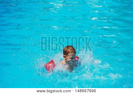 Happy Kid Playing In Blue Water Of Swimming Pool.