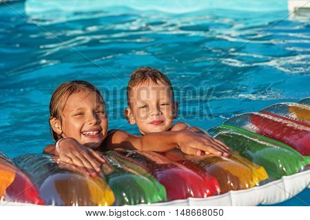 Happy Kids Playing In Blue Water Of Swimming Pool.