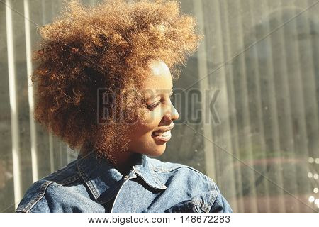 Profile Of Young Fashionable African Female With Stylish Haircut And Facial Piercing, Dressed In Den