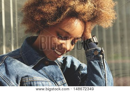 Good-looking African Woman With Ring In Her Nose, Posing Outdoors Against Gray Wall Background, With