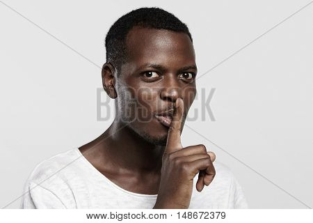 Body Language. Young African Man In White T-shirt Holding Finger On His Lips, Asking To Keep Silence