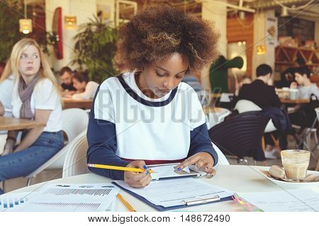 Dark-skinned Student Girl Holding Her Fingers On Touch Screen Tablet, Doing Home Assignment, Prepari
