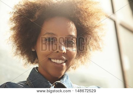 Outdoor Portrait Of Attractive Dark-skinned Woman With Curly Hair Wearing Denim Jacket, Enjoying Nic