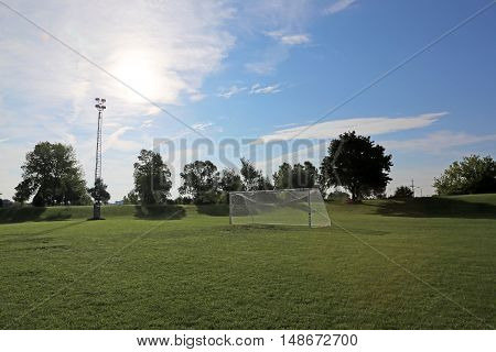 A view of a net on a vacant soccer pitch in morning light. (Sunny Soccer Field)