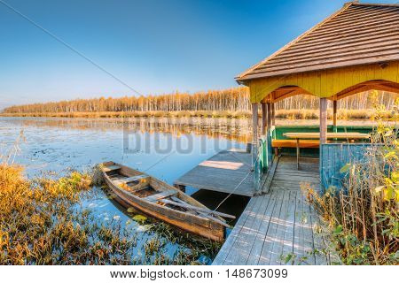 River and rowing fishing boat at beautiful sunrise in autumn evening. Old wooden boat