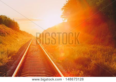 The Scenic Landscape With Railway Going Straight Ahead Through Summer Hilly Meadow To Sunset Or Sunrise In Sunlight. Lense Flare Effect.