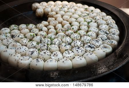 Sheng Jian Bao, Shanghai-style pan-fried buns on a frying plate sprinkled with black sesame.