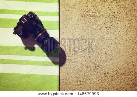 Top view of sandy beach with towel and digital SLR