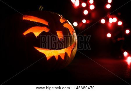 Carved Face Of Pumpkin Glowing On Halloween On Red Bokeh Light Background