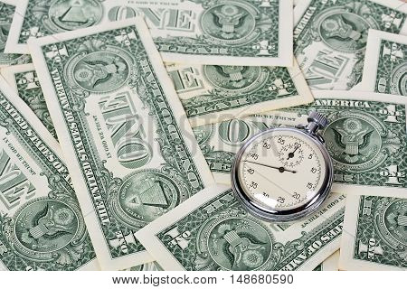 Time is money. One dollar banknotes and stopwatch