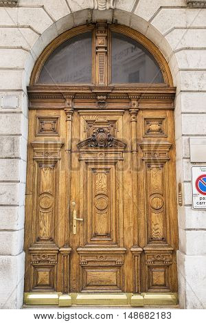 Massive wooden door on a marble decorative facade
