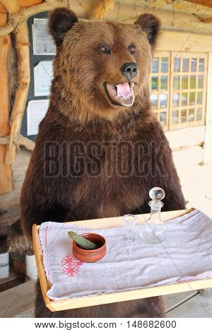 PERESLAVL-ZALESSKIY, RUSSIA - JUL 18, 2015: Bear holding a tray with a decanter and a glass and pickled cucumber in restaurant