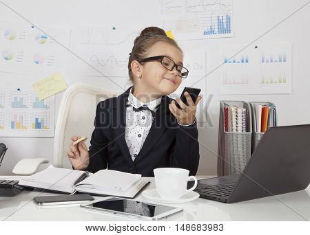 Smart little business girl doing make-up at the office