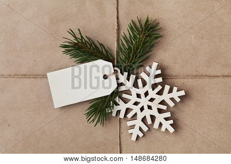 String or twine tied in a bow with tag fir tree and wooden snowflake on kraft paper texture. New Year or Christmas gift or present concept.
