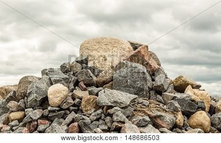 big pile of rocks and boulders piled in a heap under a grey dark cloudy sky in summer time