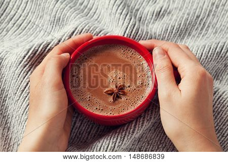 Womans hands holding a cup of hot cocoa or hot chocolate on knitted background, traditional beverage for winter time. Lifestyle photo.