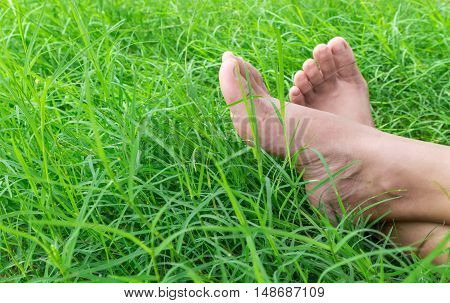Woman bare feet on green grass relax and holiday concept